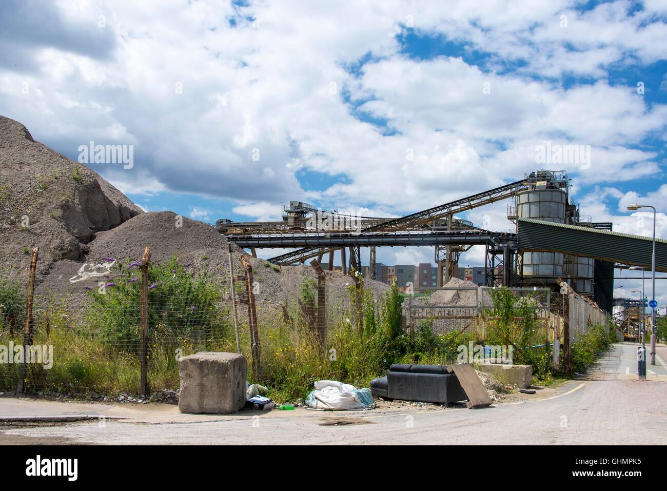 Fly tipped furniture and rubbish in front of gravel aggregates processing plant viewed from the Thames Path East - Stock Image