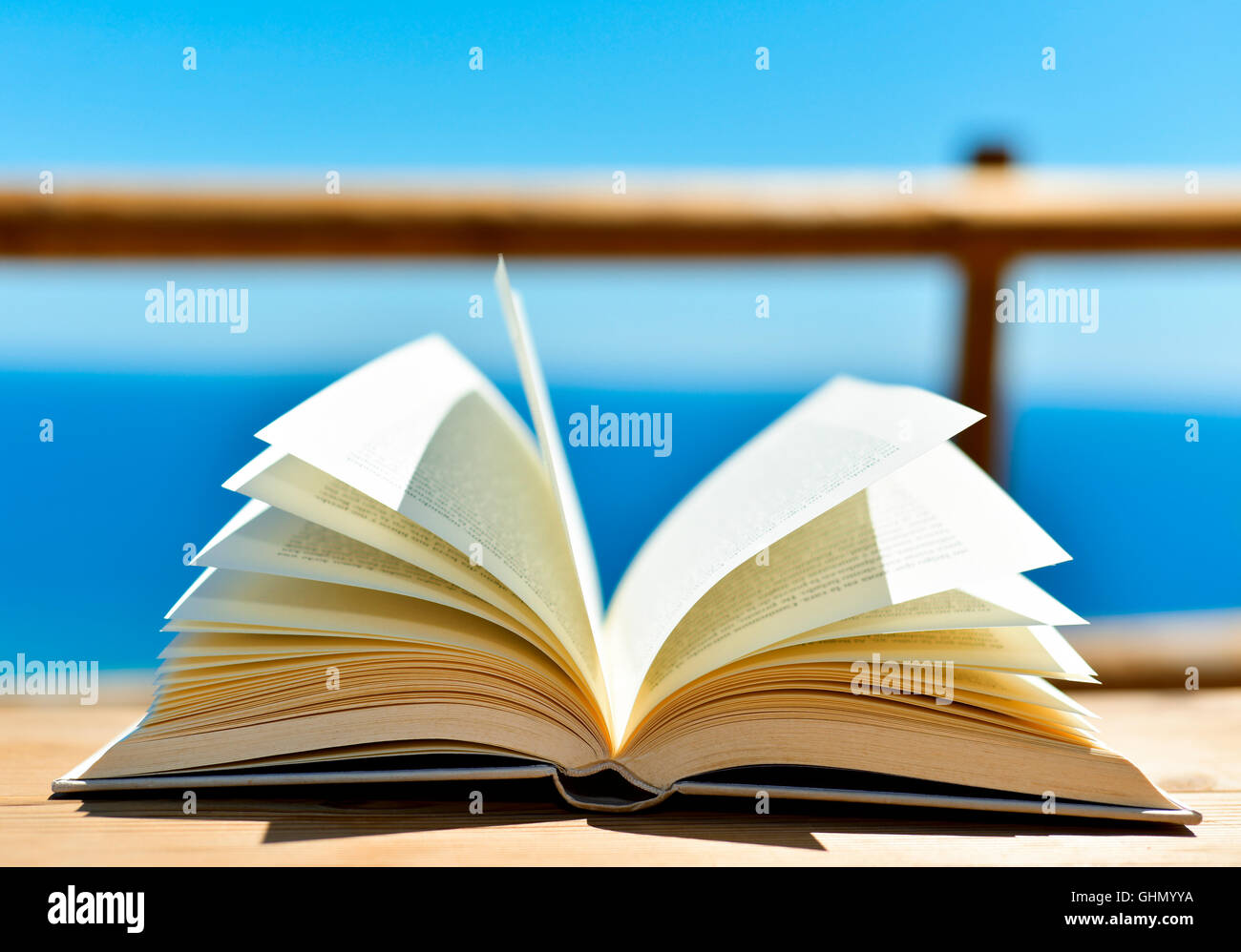 closeup of an open book on a wooden table outdoors, with the ocean in the background - Stock Image