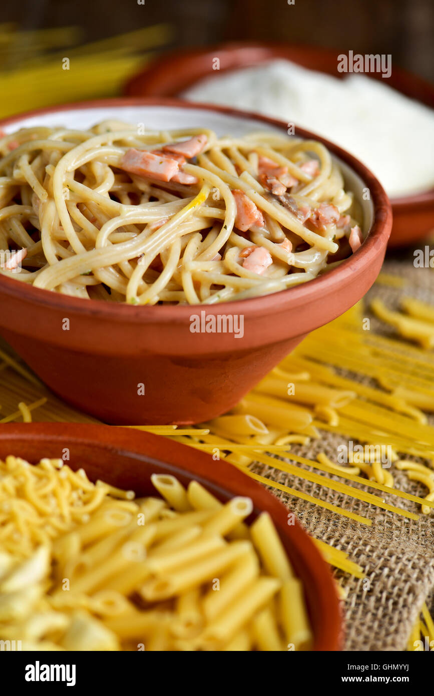 closeup of an earthenware plate with some uncooked pasta, an earthenware bowl with spaghetti alla carbonara, and - Stock Image