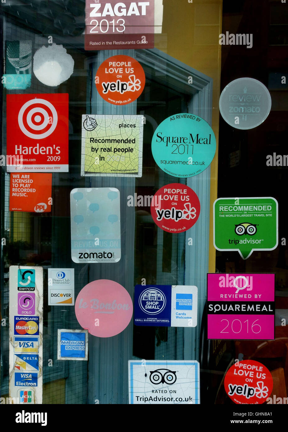 Various food recommendation stickers in restaurant window london stock image