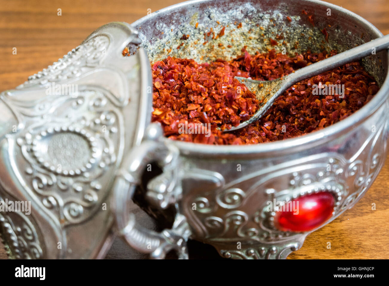 Ground red chili pepper in an ancient silver container with a spoon Stock Photo