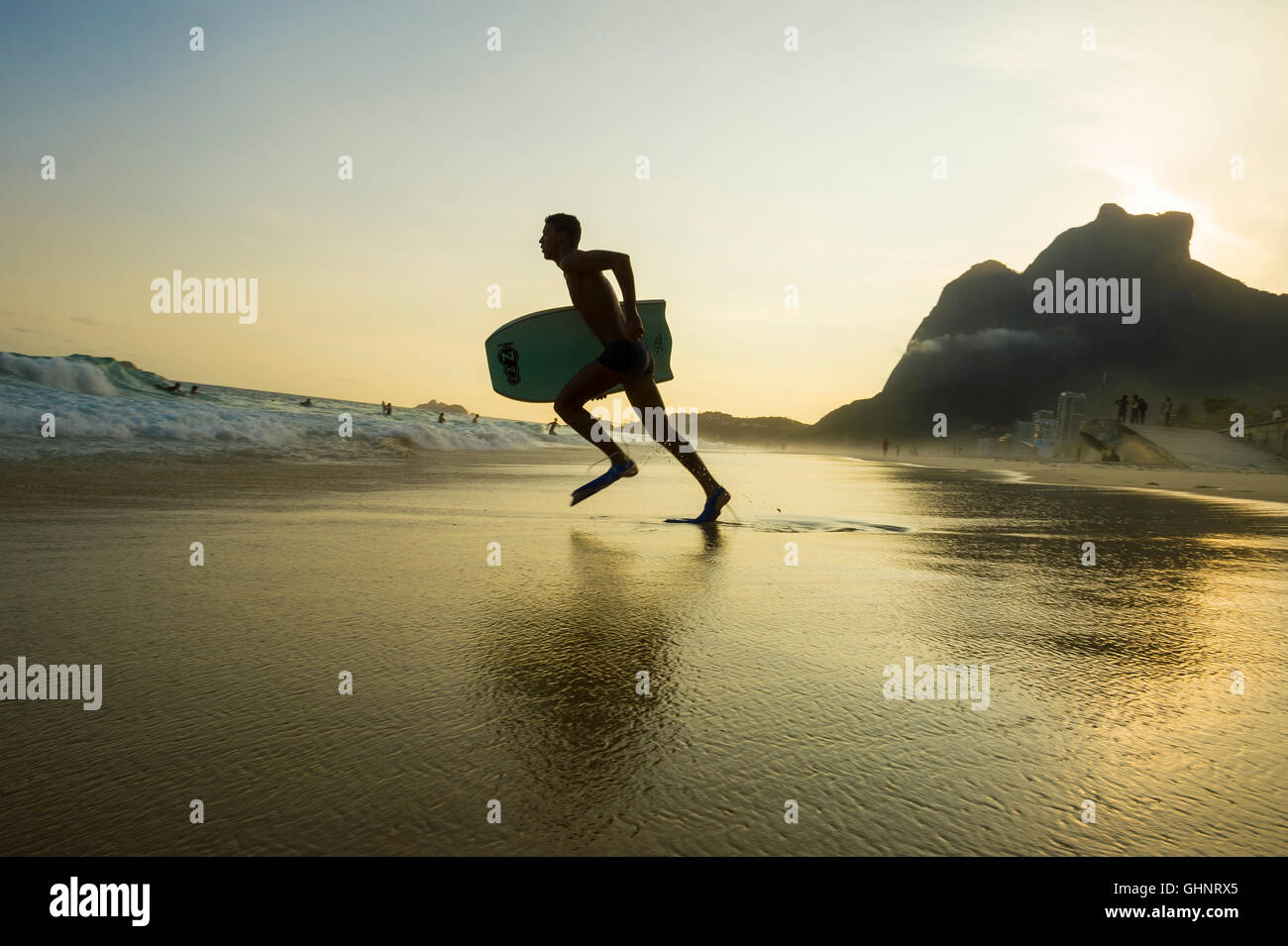 RIO DE JANEIRO - MARCH 8, 2016: Bodyboarder runs into the waves on São Conrado Beach under a sunset silhouette. - Stock Image