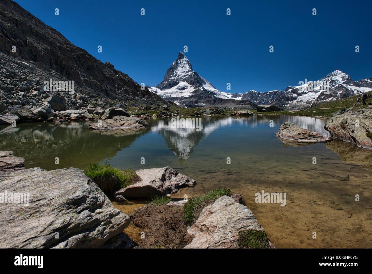 The Matterhorn reflected in a tarn below the Riffelsee, Zermatt, Switzerland - Stock Image