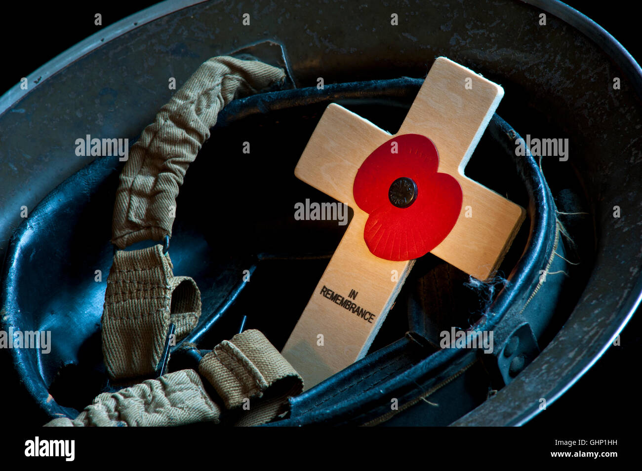 REMEMBRANCE POPPY CROSS Evocative study of WW2 original 1939 army soldier tommy military helmet with Remembrance - Stock Image