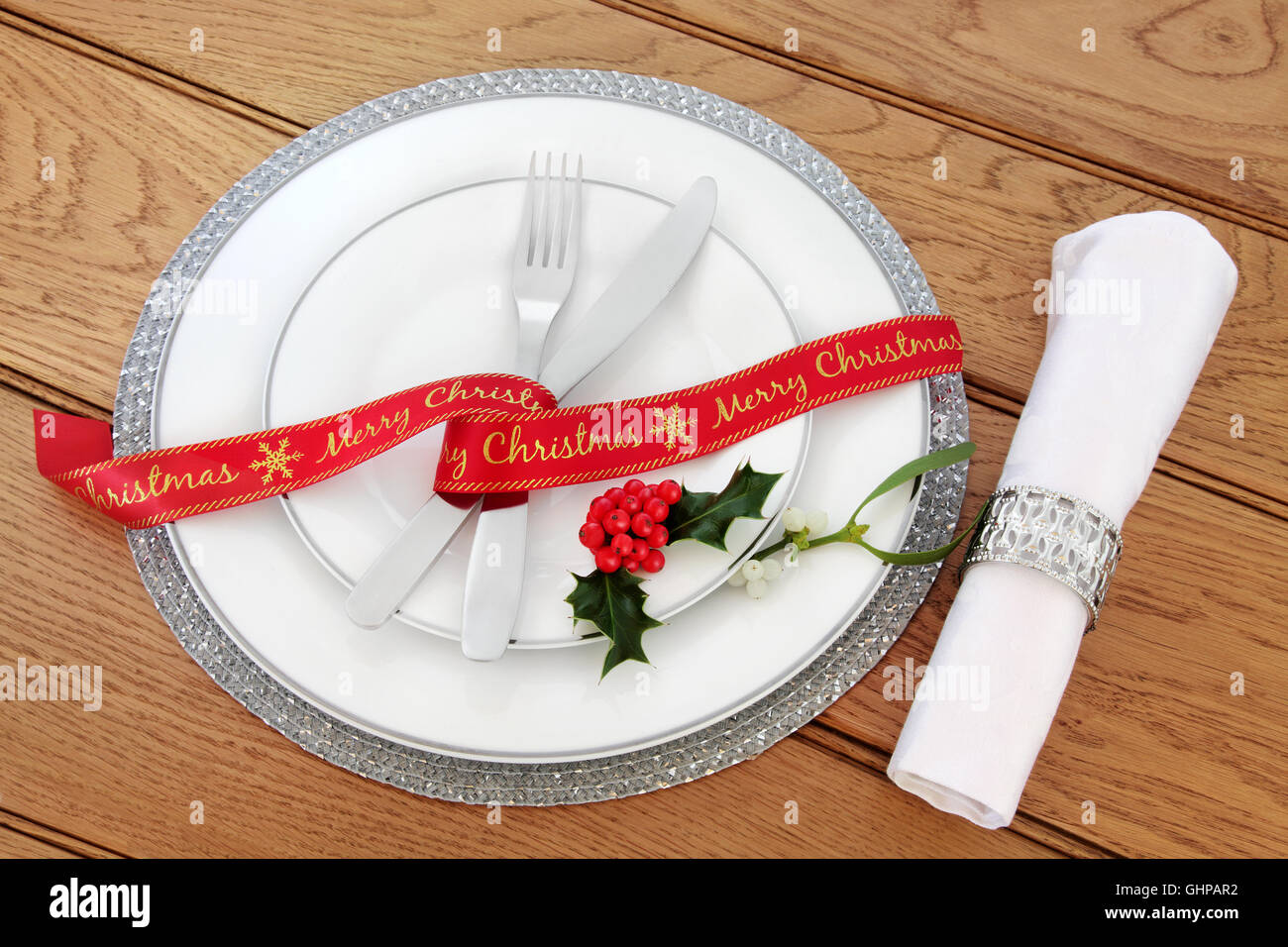 Simple christmas dinner table setting with white porcelain plates red ribbon knife and fork linen serviette and silver ring. & Simple christmas dinner table setting with white porcelain plates ...
