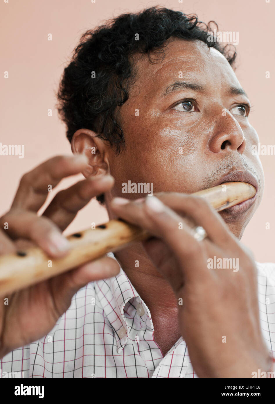 Wind instrument maker Yim Seychot plays a Cambodian flute at his home outside Phnom Penh, Cambodia. - Stock Image