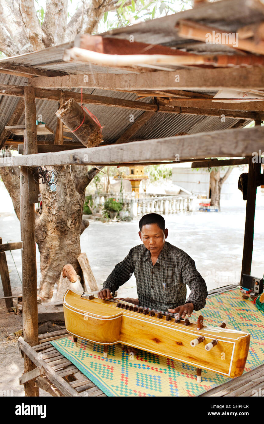 Teacher Teav Nop plays Cambodian wedding music on a Takhe. Chambok Village, Bati District Takeo Province. Cambodia - Stock Image