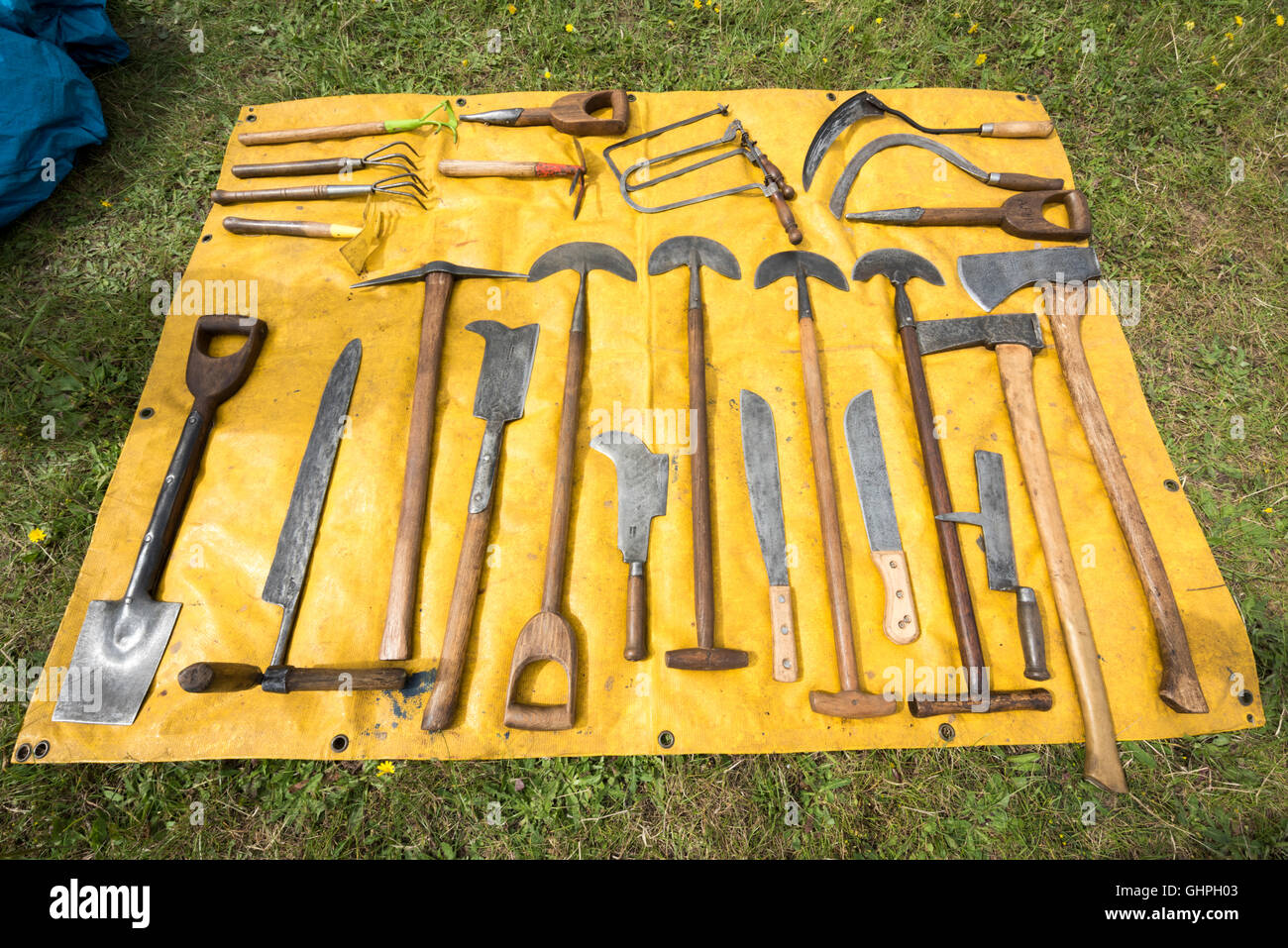 Antique gardening tools laid out on a yellow sheet for sale at a car boot sale - Stock Image