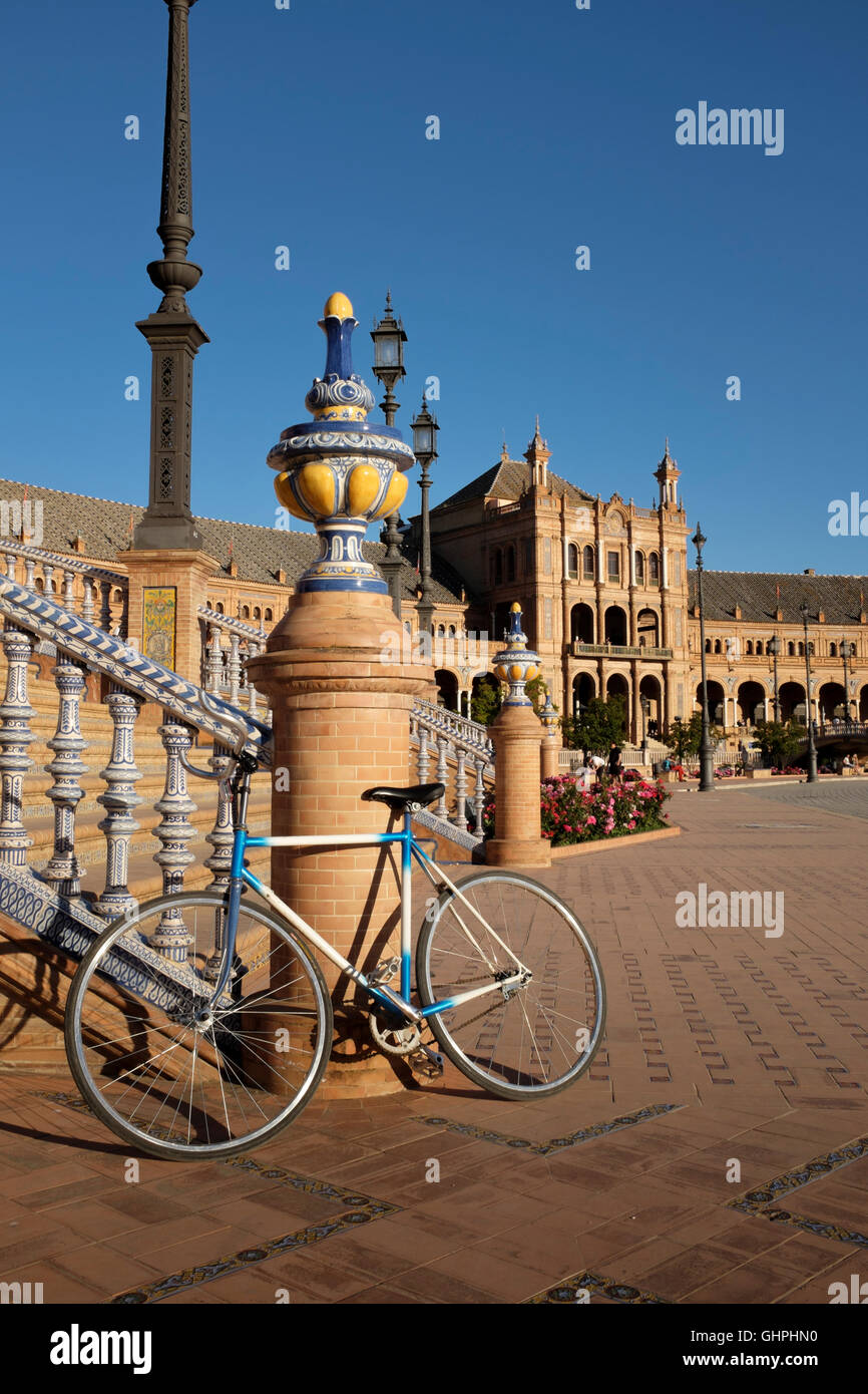 A bicycle propped against one of the bridges at Plaza de Espana, in Parque María Luisa, Seville, Spain. - Stock Image