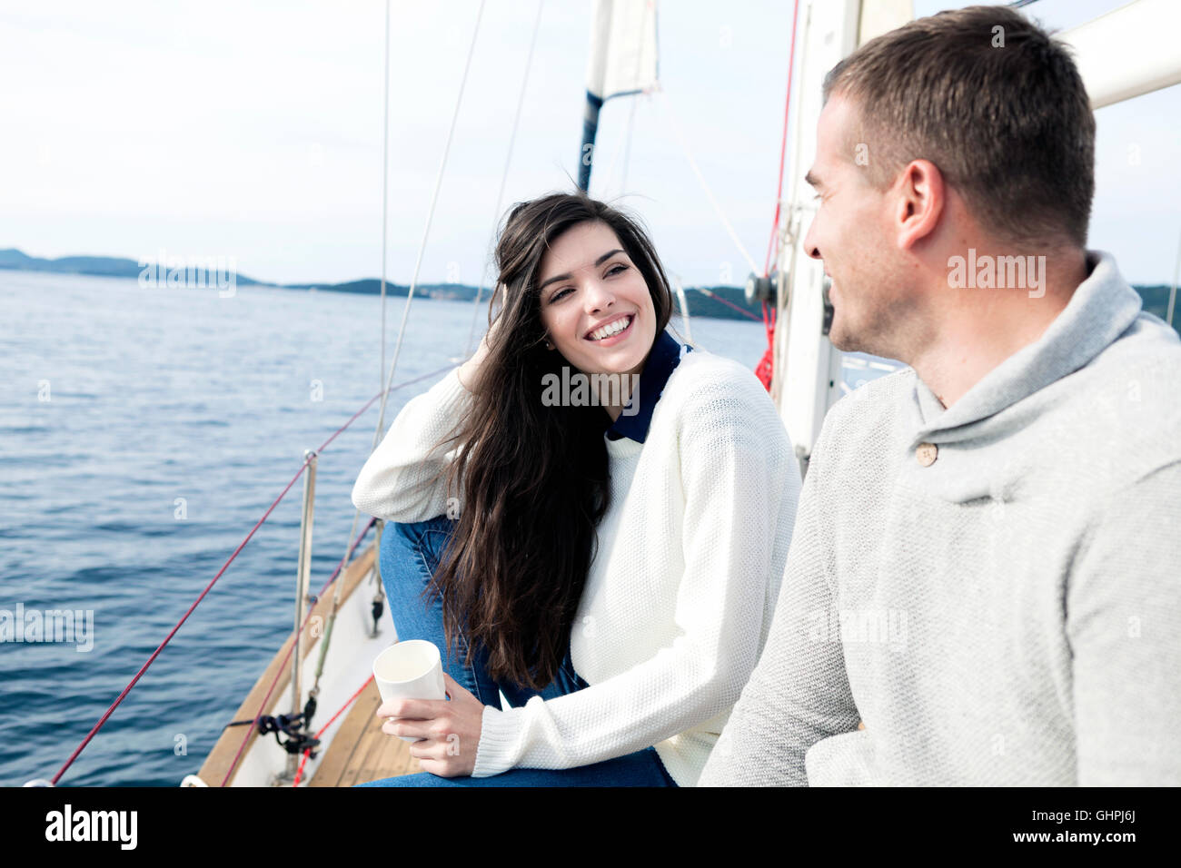 Young couple on yacht looking at each other - Stock Image