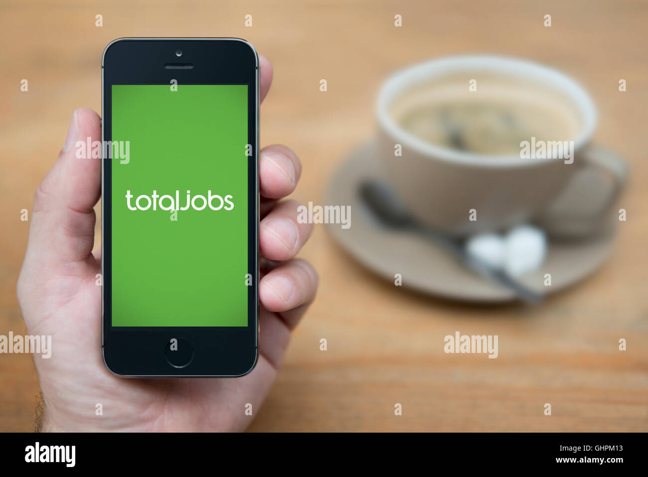 A man looks at his iPhone which displays the Total Jobs logo, while sat with a cup of coffee (Editorial use only). - Stock Image
