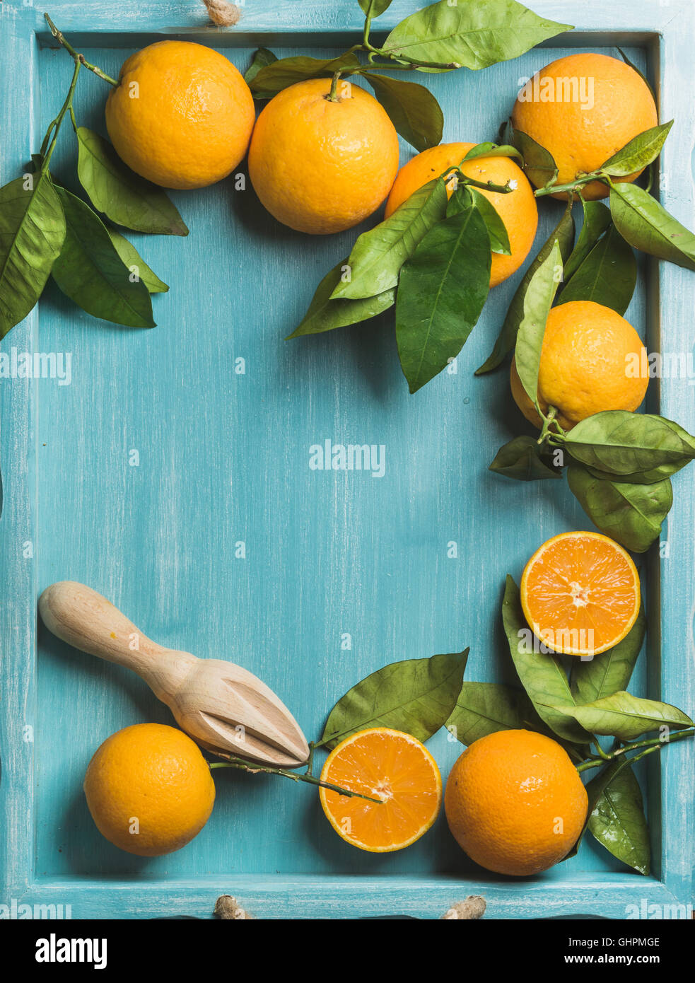 Fresh oranges with leaves on blue painted wooden background, copy space - Stock Image