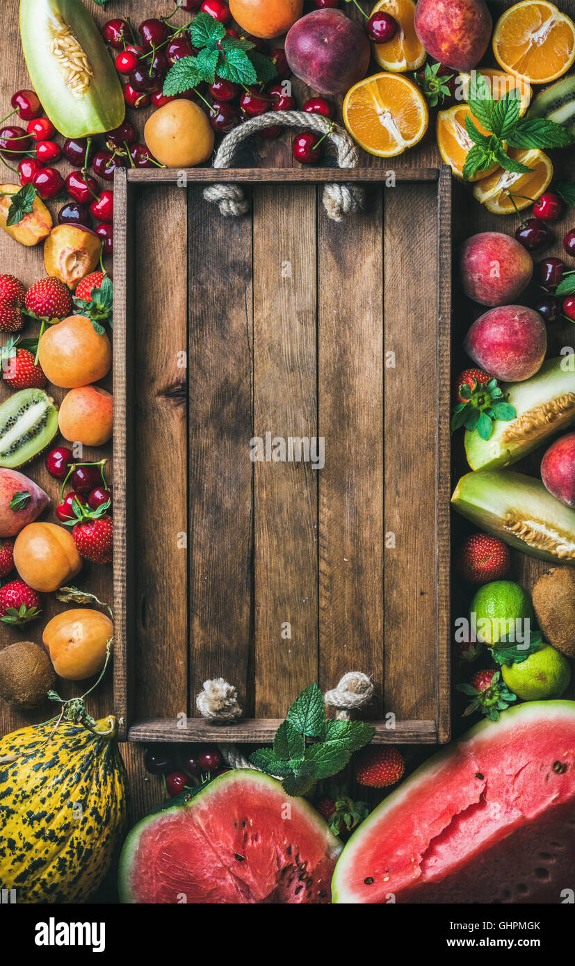 Summer fresh fruit variety with rustic wooden tray in center - Stock Image