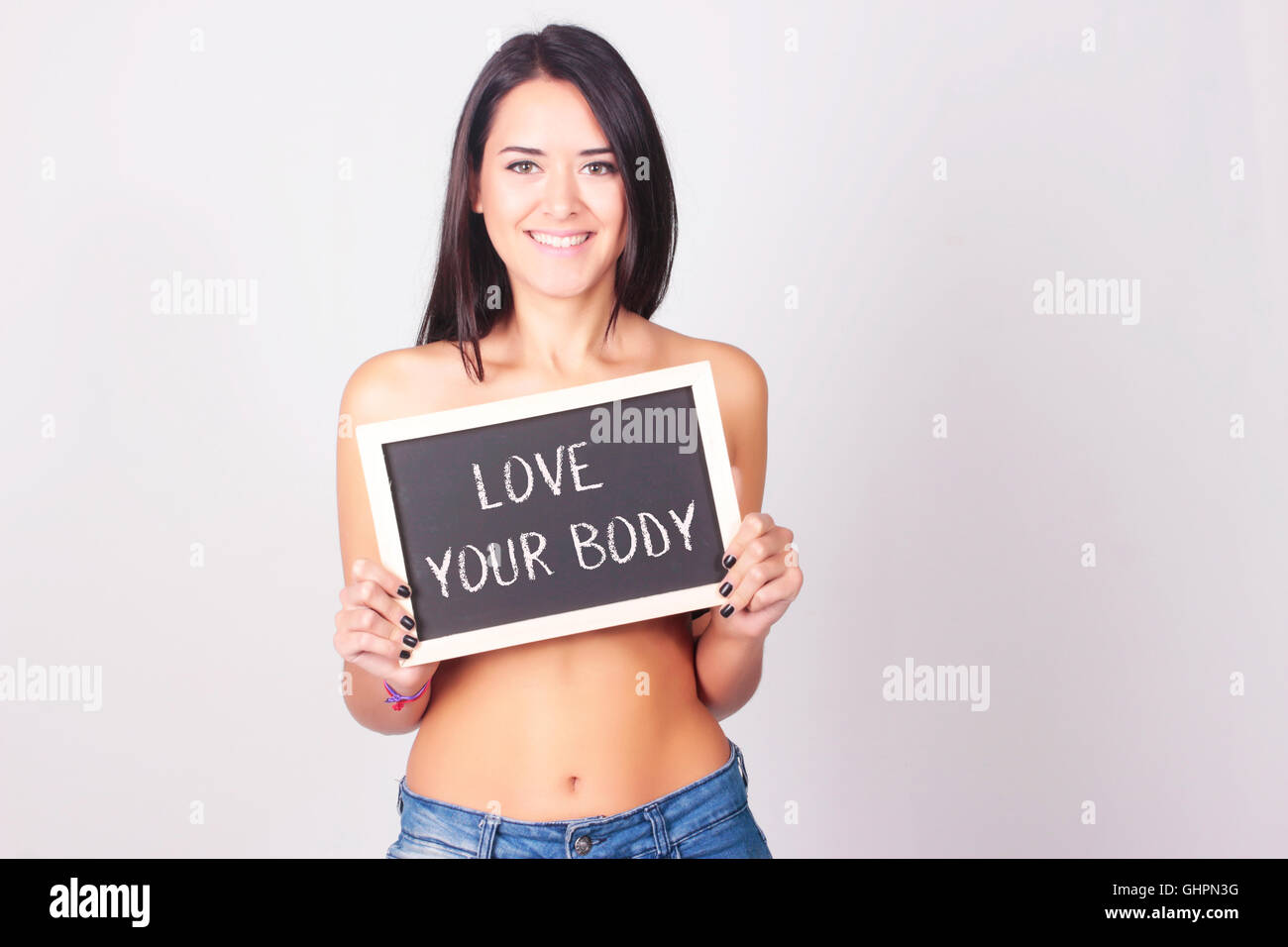 Young woman holding chalkboard that reads Love Your Body. Self love concept. - Stock Image