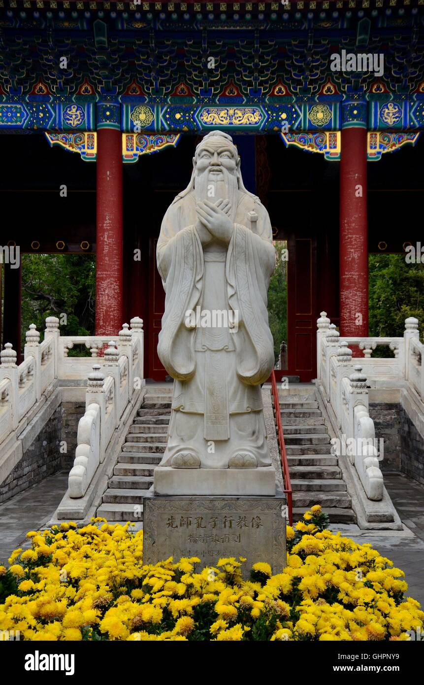 Statue of Chinese philosopher Confucius on a pedestal and surrounded by yellow flowers Beijing China - Stock Image