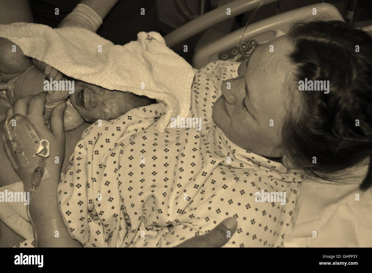 New born baby and mother in hospital bed - Stock Image