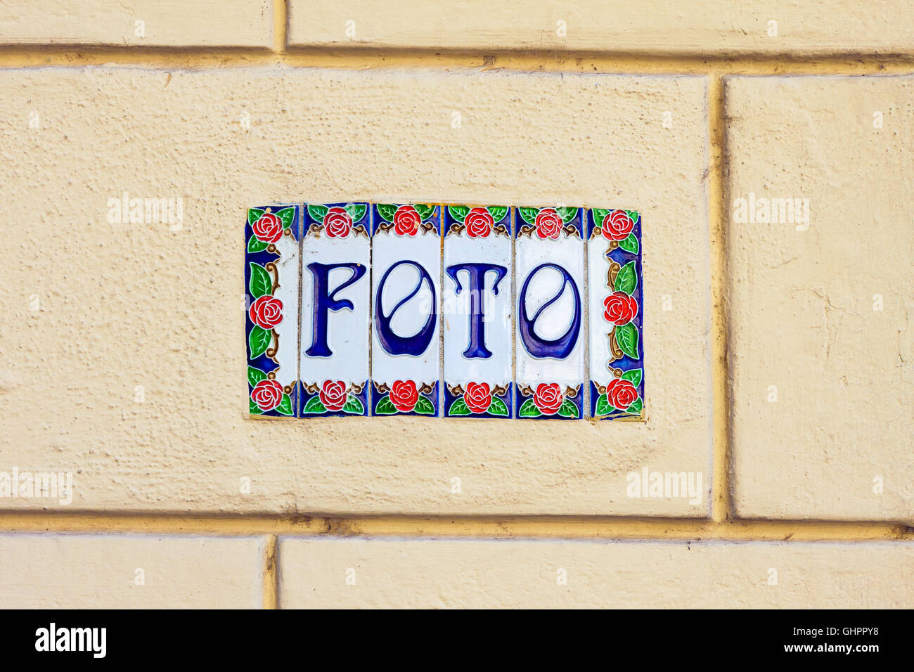 Word foto on decorative ceramic tiles on the wall outdoors - Stock Image