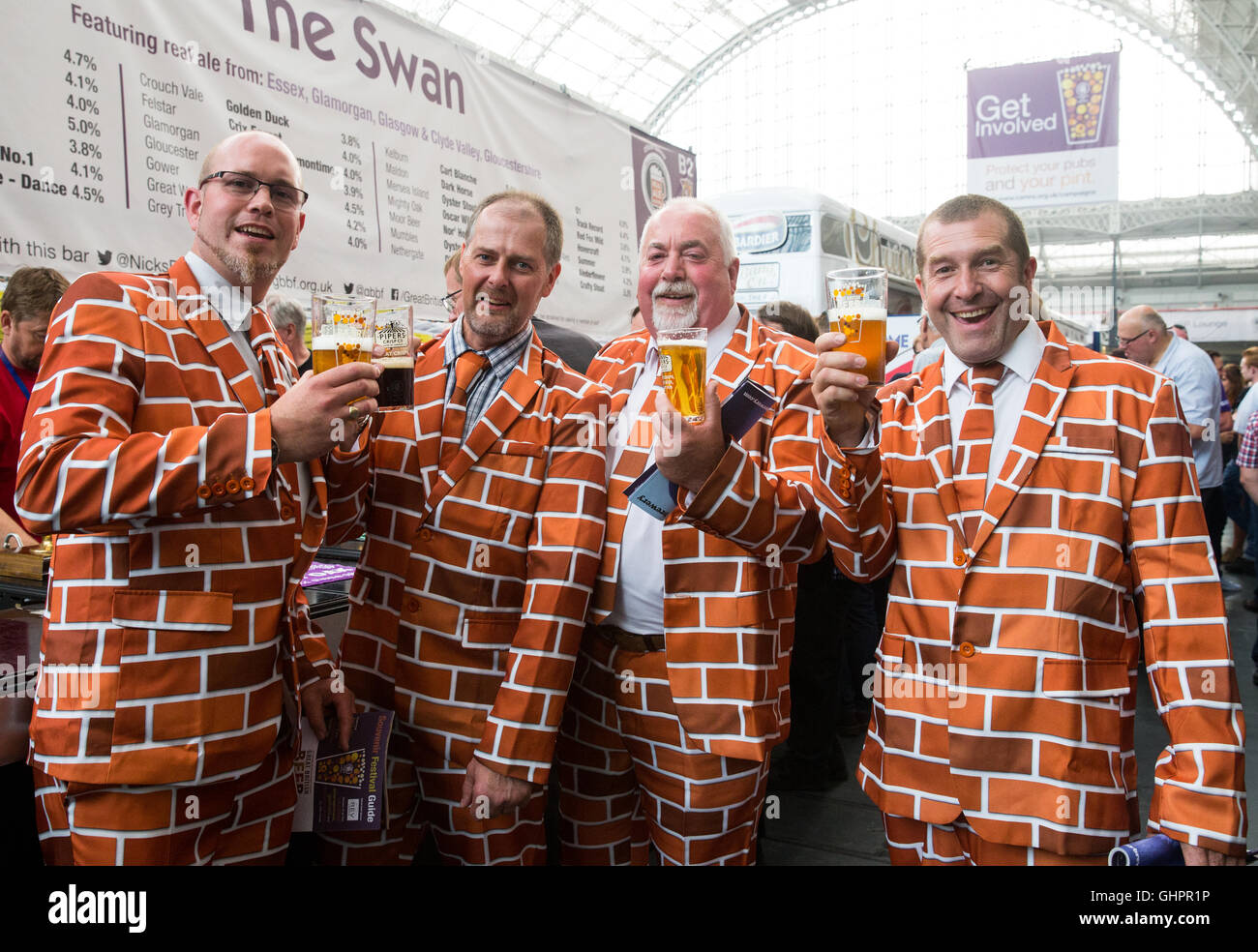 4 men drinking beer wearing  matching 'brick' style suits at the Great British Beer festival at Olympia,West - Stock Image