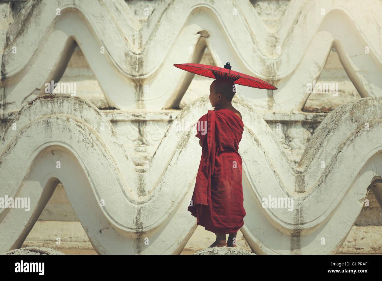 Burma Novice monk holding red umbrella  standing on the pagoda Stock Photo