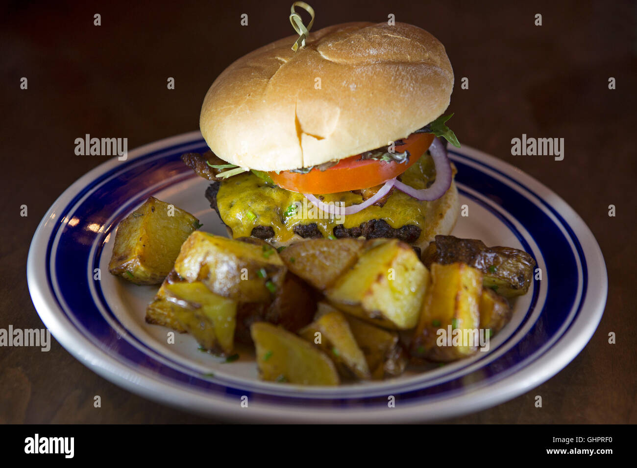 A cheeseburger served with potatoes at Carbonaer in Newfoundland and Labrador, Canada. The potatoes are dusted with - Stock Image