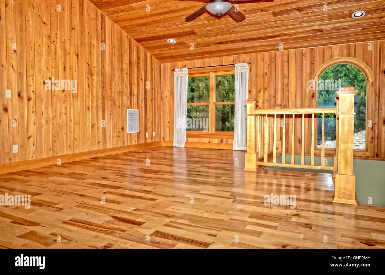 An empty room in a new modern home.  Hickory floors, cypress walls and ceiling and a stairway. - Stock Image