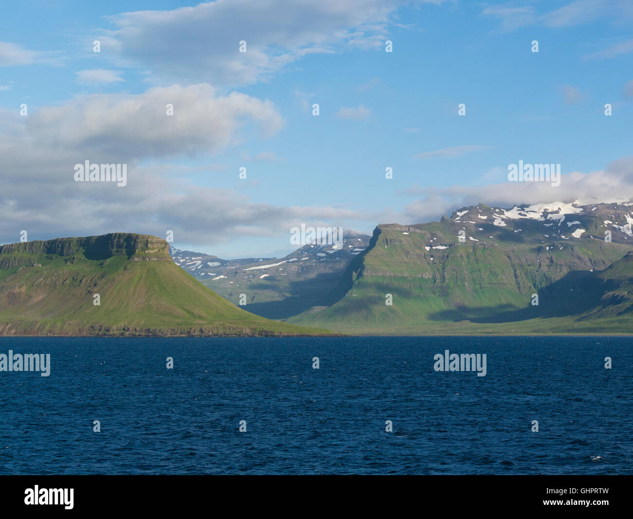 Rugged coastline of Snaefellnes Peninsula Iceland from Faxaflói Bay  on a lovely July summers day with snow topped Stock Photo