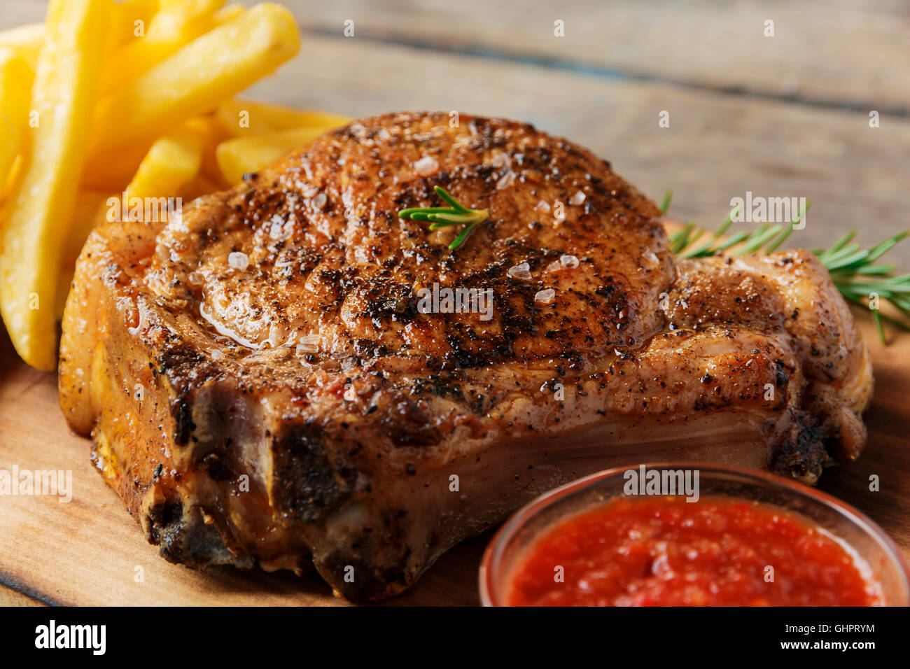 steak on the bone steak with french fries and sauce - Stock Image