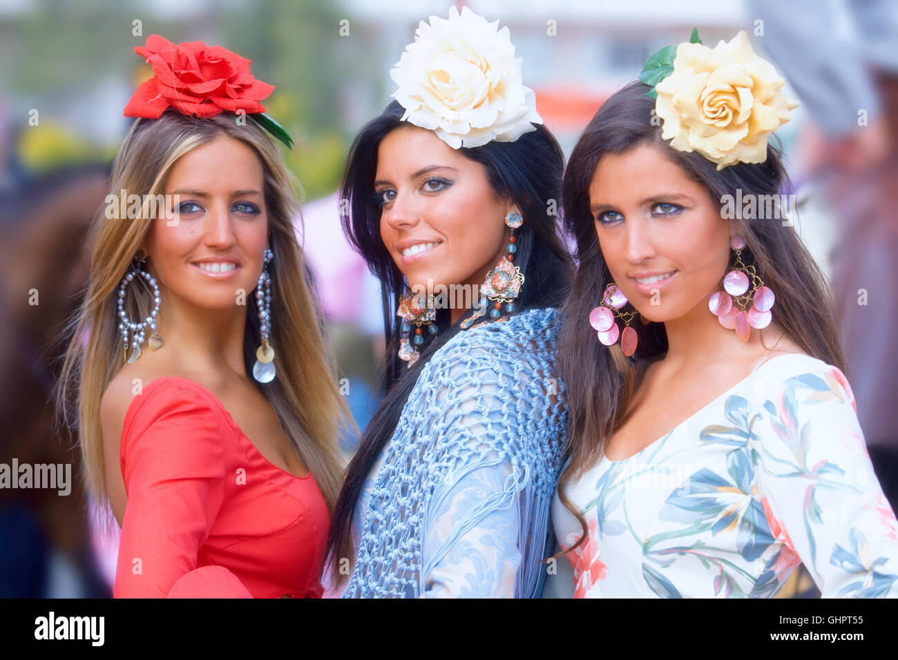 Three girls in traditional dress during the  Sevilla fair, Spain - Stock Image