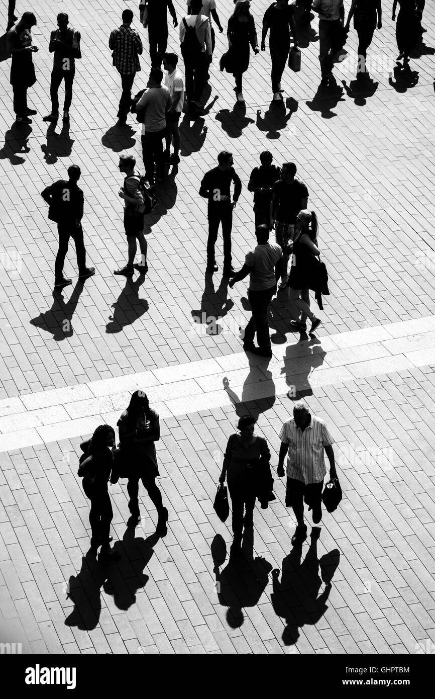 People and their shadows are silhouetted against a block paved area. The image is from a high angle - Stock Image