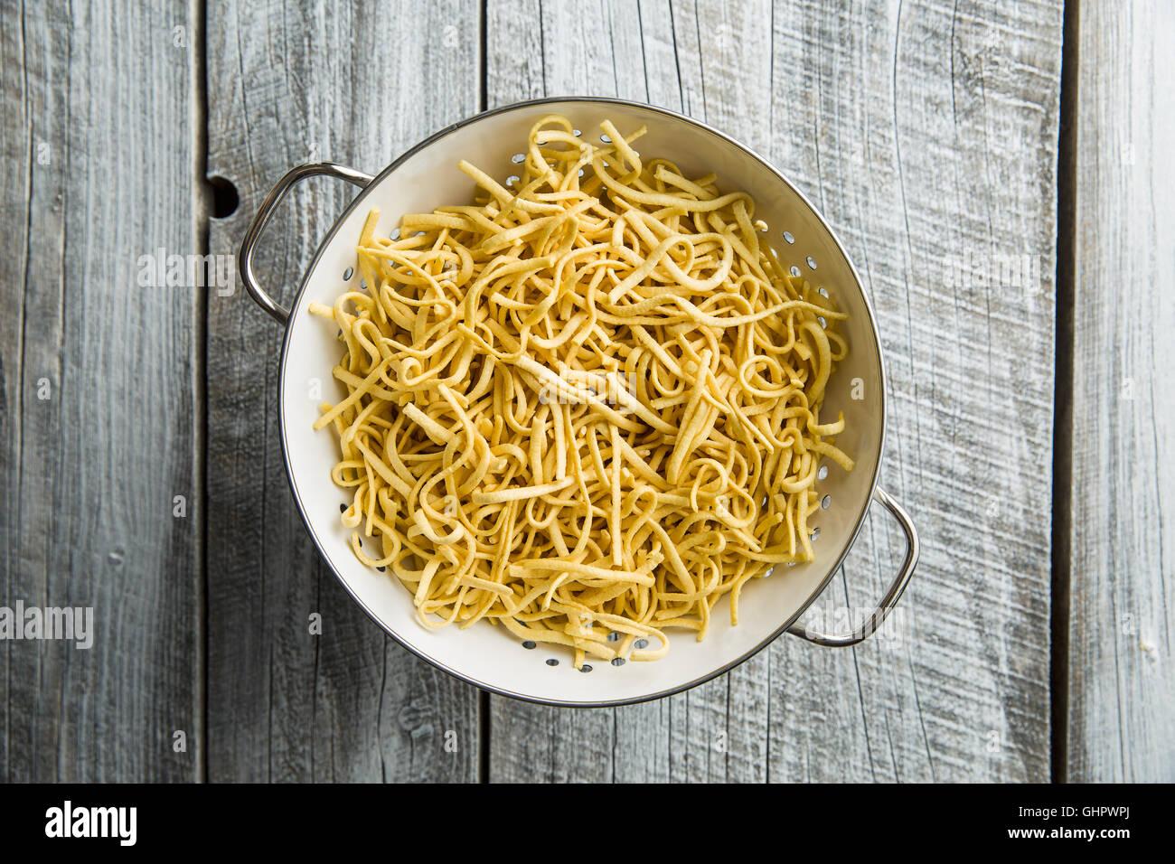 Tasty spaetzle pasta in colander. - Stock Image
