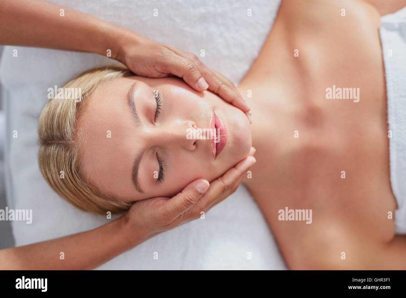 Top view shot of a beautiful young woman getting a facial massage at a spa - Stock Image