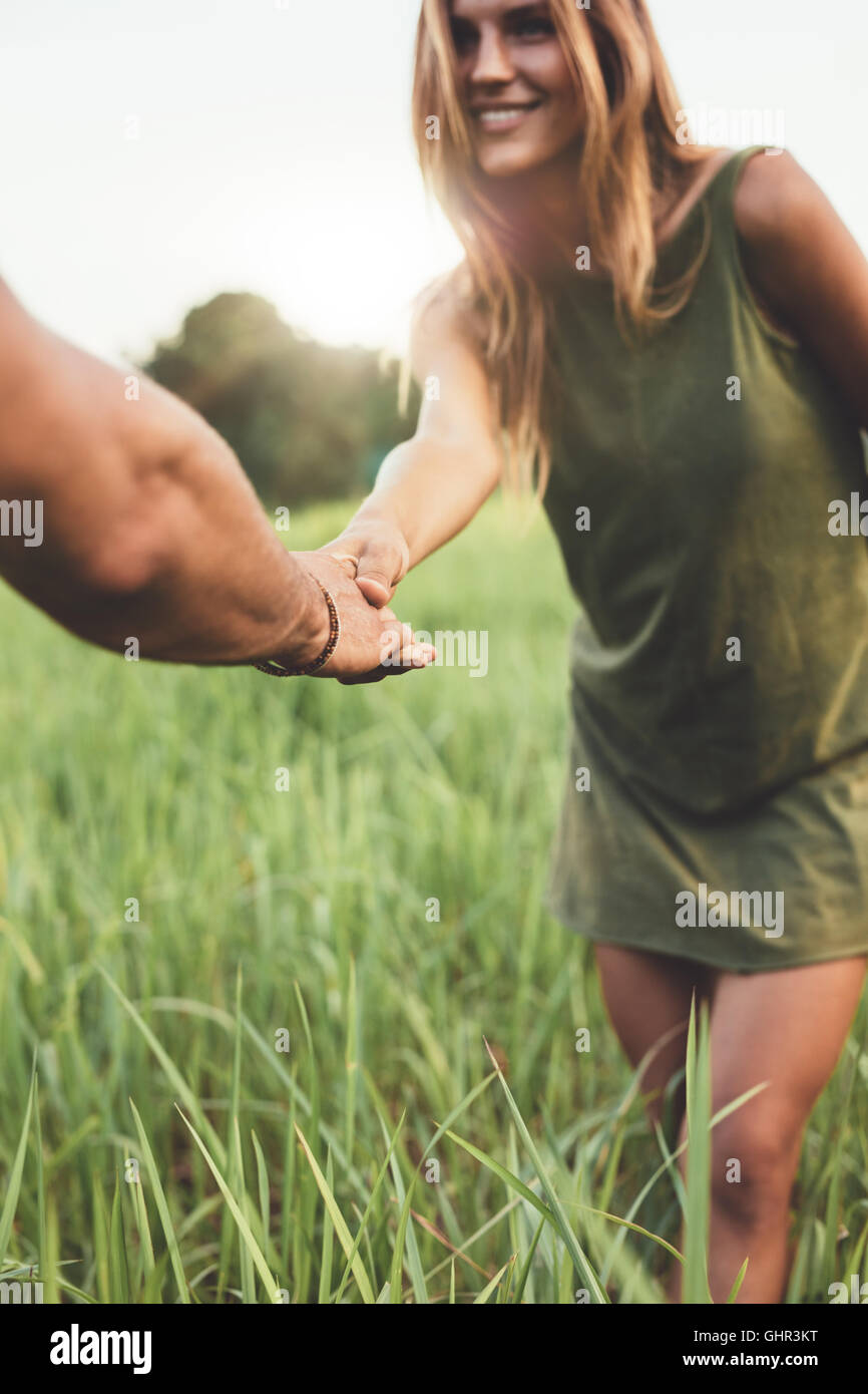 Shot of woman holding hand of her boyfriend and standing in grass field. Loving young couple on meadow outdoors. - Stock Image