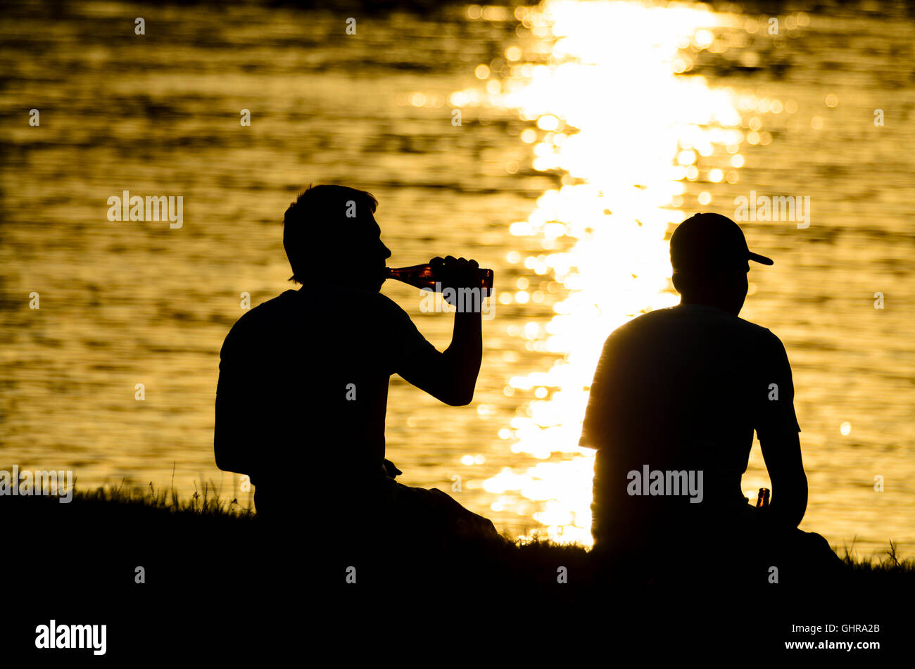2 youthful teenager teenagers beer drinkers along the Danube River, setting sun, Austria, - Stock Image