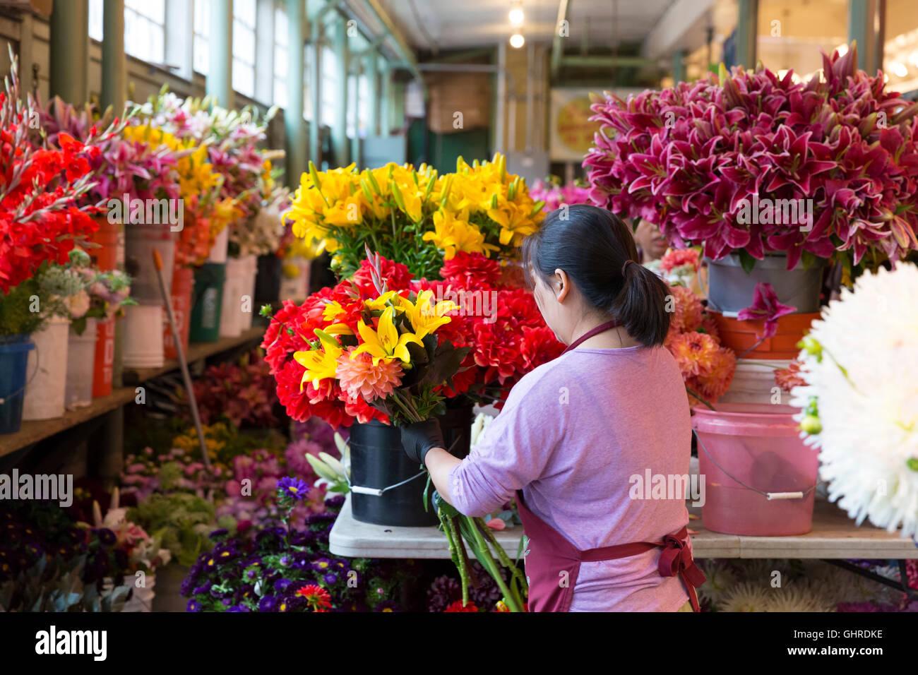 Seattle, Washington: A merchant arranges bouquets of summer flowers ...