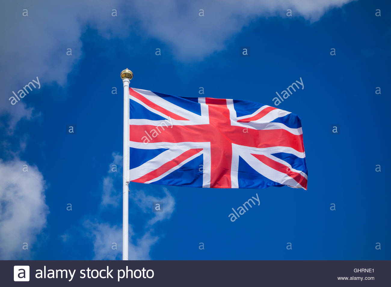 Union Jack flag on a flagpole against a bright blue sky with white clouds - Stock Image