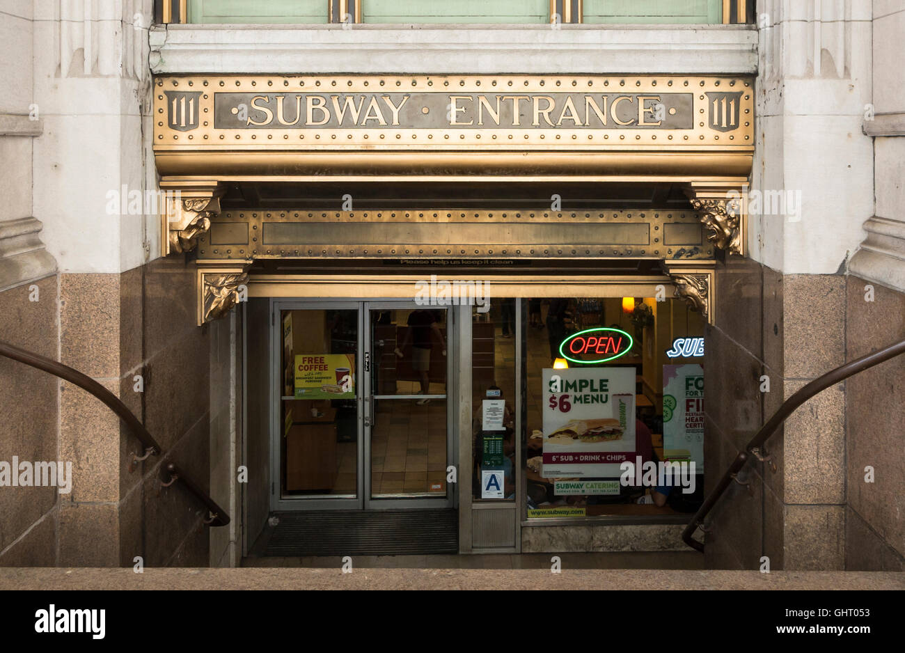 Wall Street subway entrance with ornate gold art deco sign and Subway restaurant below. New York. - Stock Image