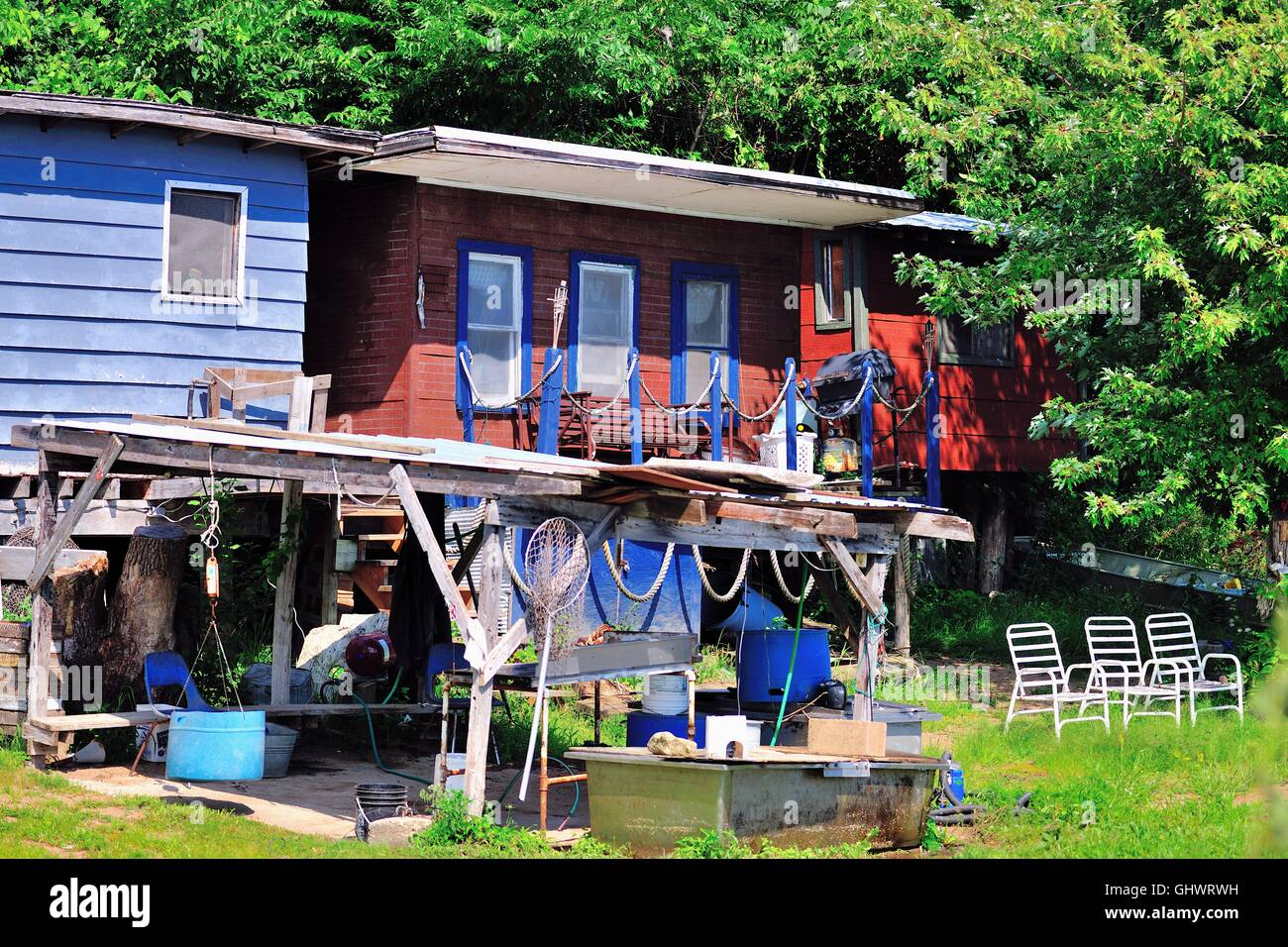 Chairs aligned to provide a view and fishing nets hanging on protected shelter at these homes sit along the Mississippi - Stock Image