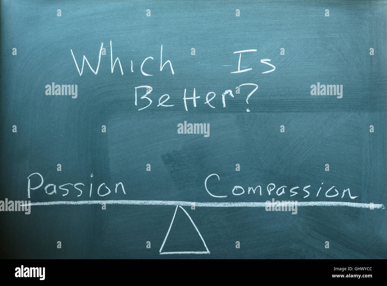 the words passion and compassion on a scale in equilibrium written on a chalkboard. - Stock Image