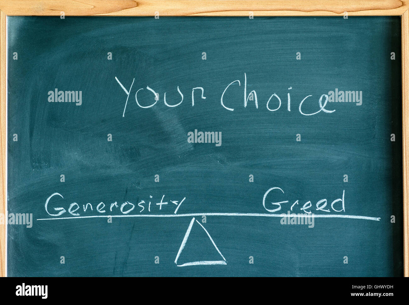 the words generosity and greed on a scale in equilibrium written on a chalkboard. - Stock Image