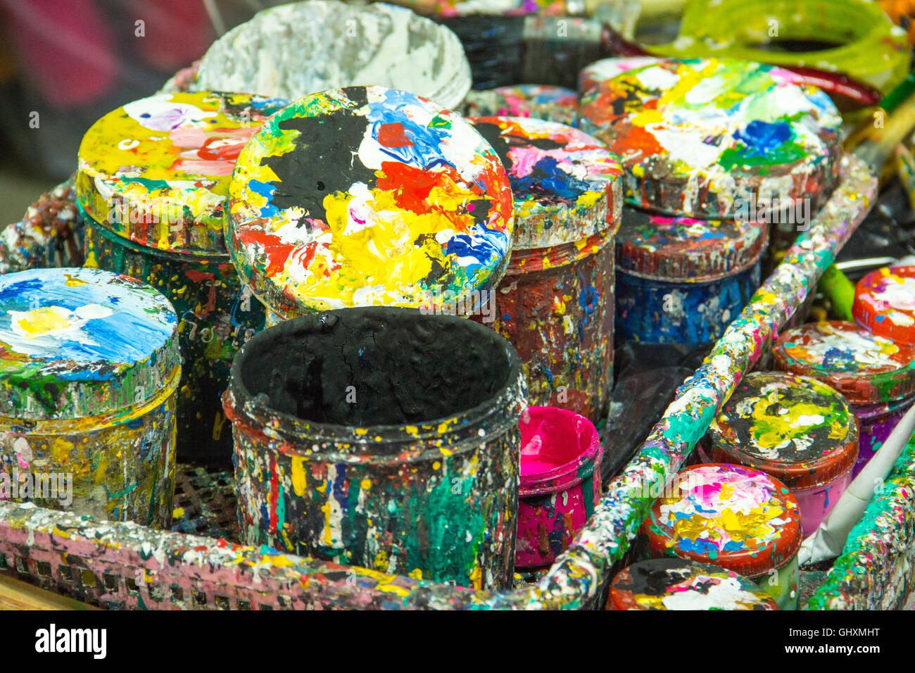 Paint-splattered tins of artist's paints and brushes, Stock Photo