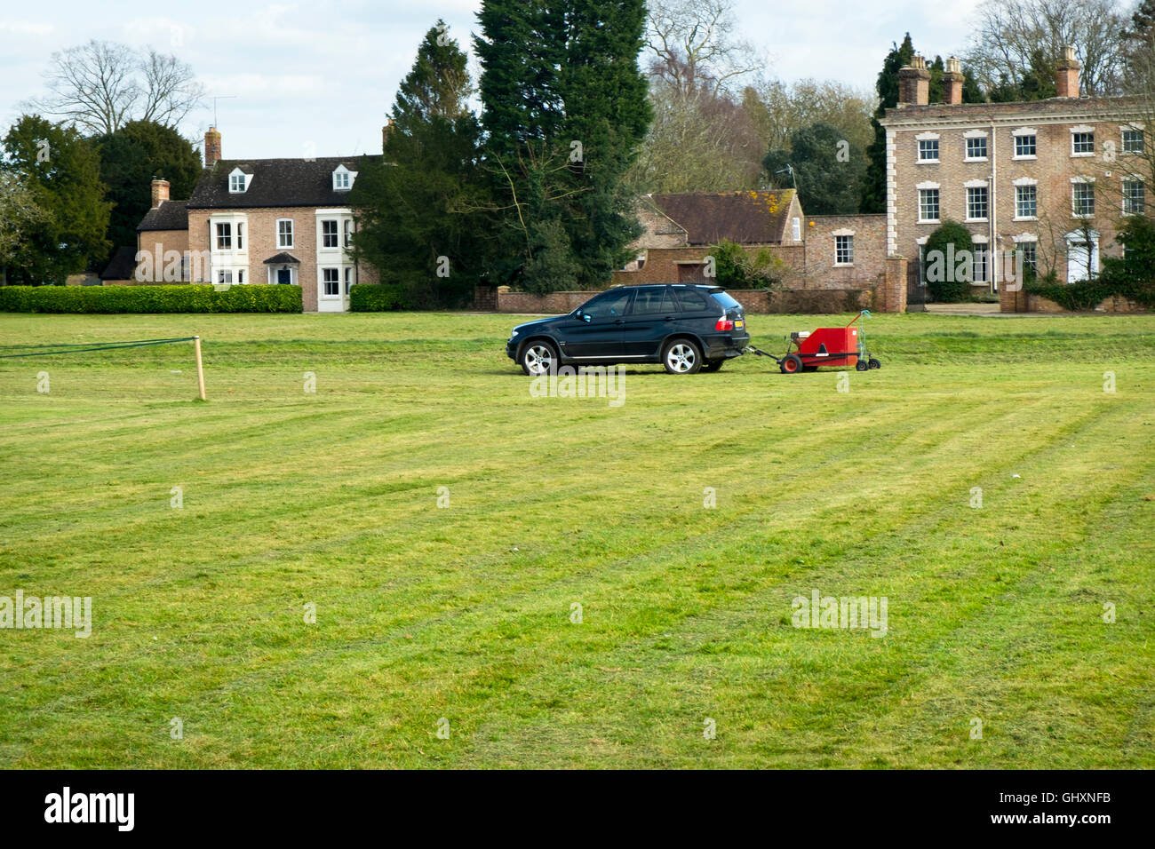 Towing a mowing machine with a BMW car. Mowing the cricket pitch at Frampton on Severn, Gloucestershire, UK - Stock Image