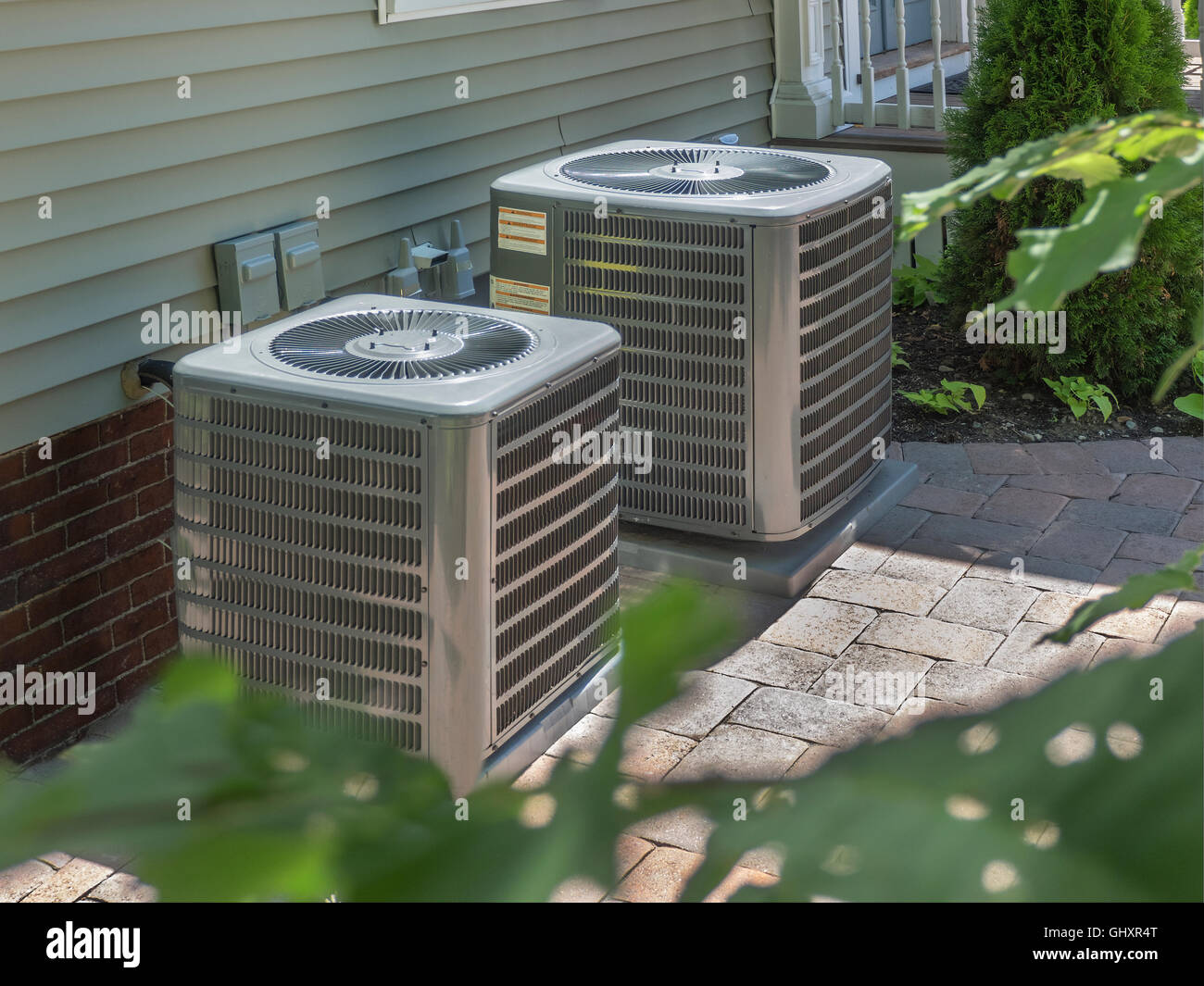 Outdoor air conditioners/heaters in back of housing complex - Stock Image