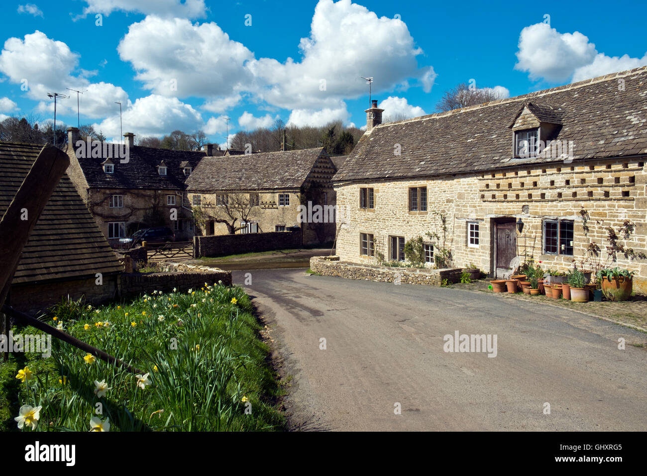 Picturesque Cotswold cottages cluster around the Dunt Stream ford in spring sunshine, Duntisbourne Leer, Cotswolds, - Stock Image