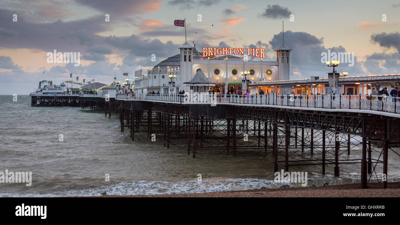 A panoramic photograph of Brighton Pier with a colourful evening sky - Stock Image