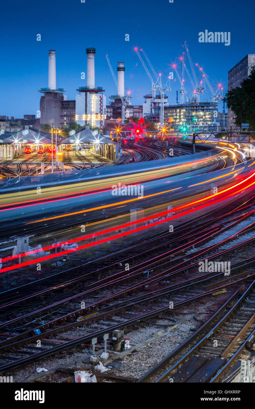 Trains leave light trails as they move past the construction site of Battersea Power Station - Stock Image