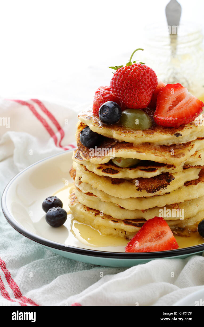 Stack of hot pancakes with fruits, food closeup - Stock Image