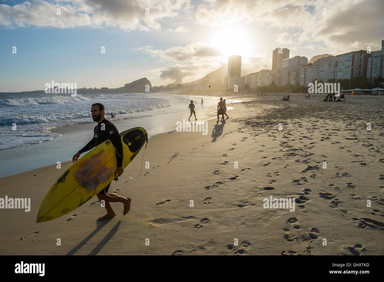 RIO DE JANEIRO - OCTOBER 30, 2015: A Brazilian surfer heads to the sea as a group plays altinho on Copacabana Beach. - Stock Image