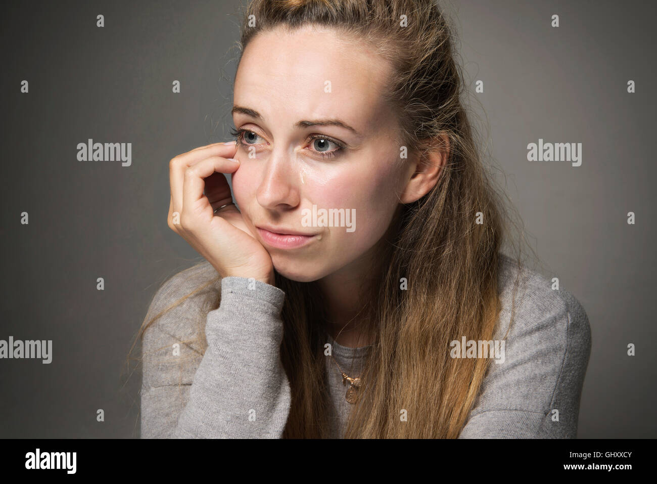 Sad young woman close up tears running down face looking in despair hand resting on chin looking away sadness concept - Stock Image