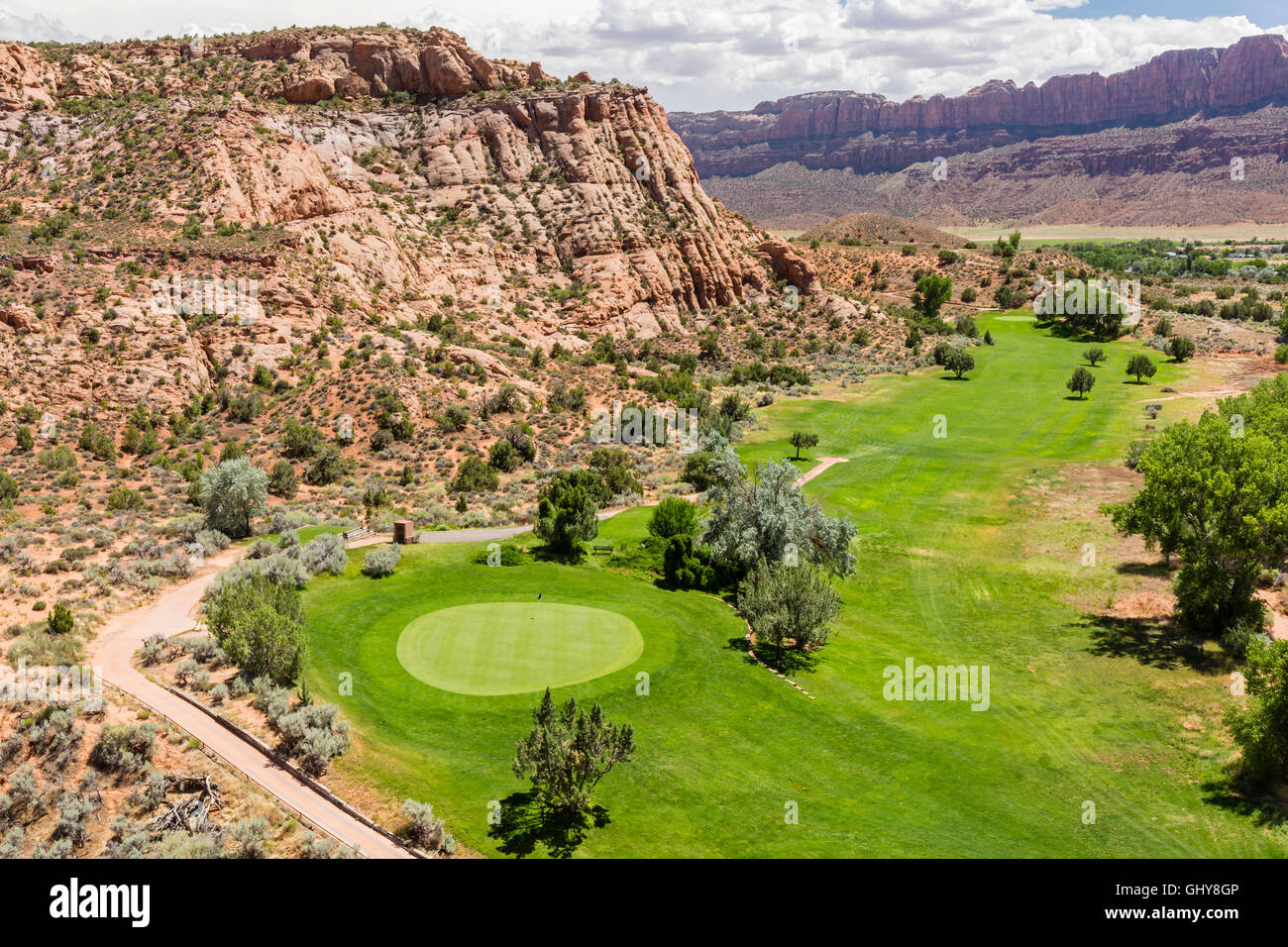 The 4th Green of the Moab Golf Course nestled under a red rock cliff in Moab, Utah. - Stock Image