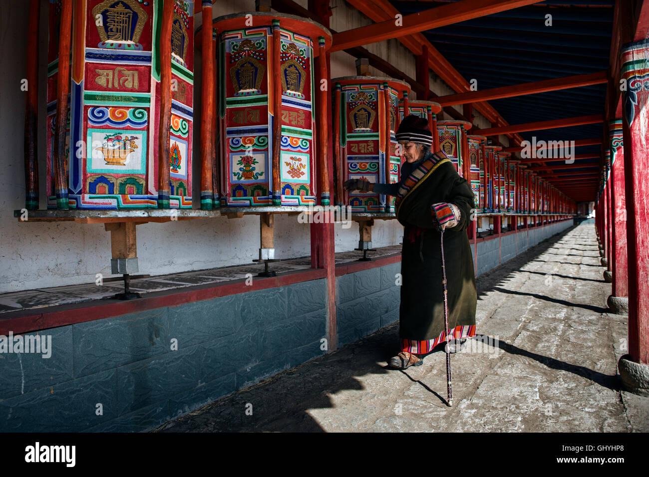 Walking while rotating the prayer wheels - Stock Image